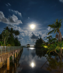 Gazebo and moon in water's reflection. Night landscape