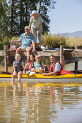 Portrait of smiling family on dock and in kayaks on lake