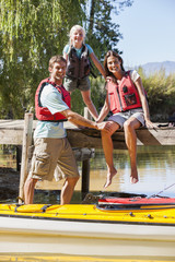 Portrait of happy family on dock over lake