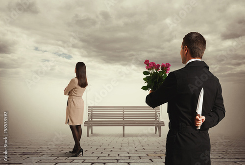 man holding flowers and knife behind back