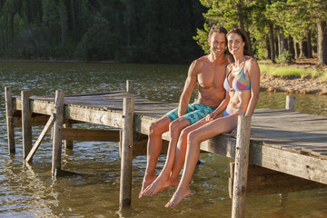 Happy couple sitting at the edge of dock over lake