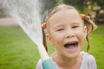 Happy girl pouring water from a hose