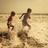 Fototapety Happy kids playing at the beach