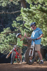 Grandfather and grandson high fiving on mountain bikes in woods