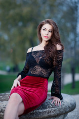 Charming young brunette woman in black lace blouse and red skirt