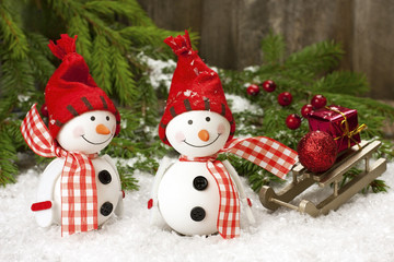 Two smiling snowmen friends in the snow
