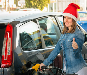 Young woman at gas station with Santa hat