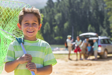 Portrait of smiling boy with fishing net at lakeside