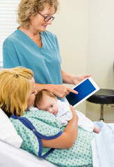 Mature Nurse Explaining Reports On Tablet To Woman With Babygirl