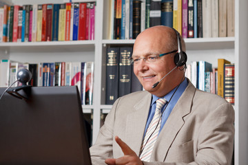 Elderly man with headphone and computer smiling