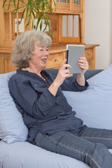 Happy aged woman with tablet pc