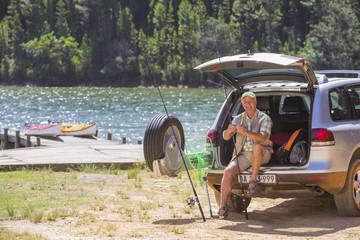 Smiling man preparing fishing rod at back of car lakeside