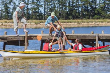 Multi-generation family getting in kayaks on lake