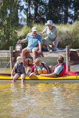 Multi-generation family on dock and in kayak on lake