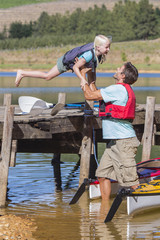 Daughter jumping off dock onto father