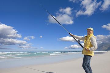 Happy senior woman fishing on sunny beach