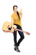Young female holding an acoustic guitar and gesturing happiness