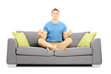 Young male meditating seated on a sofa