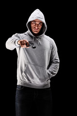 Young man with hood over his head with a gun symbolizing crime