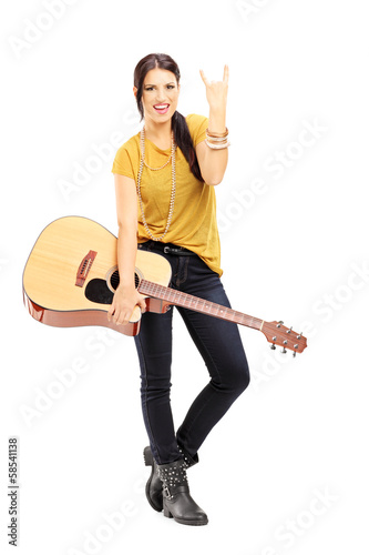 Female holding an acoustic guitar and giving rock and roll sign