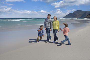Happy family walking on sunny beach