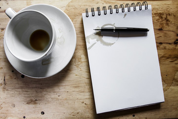 Coffee cup, spiral notebook and pen on the wooden table backgrou