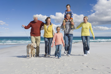 Family with dog walking on sunny beach