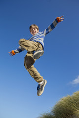 Portrait of smiling boy jumping against blue sky