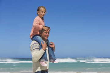 Father carrying daughter on shoulders on sunny beach