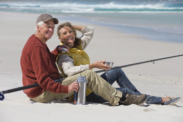 Senior couple with fishing rod drinking coffee on sunny beach