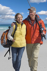 Senior couple with backpack and fishing rod on sunny beach