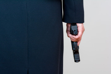 Woman holding hand gun on white background