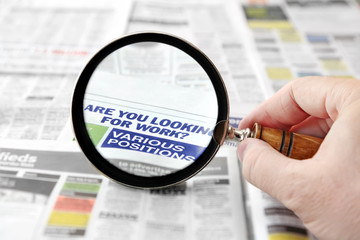 Magnifying glass over a newspaper job search section