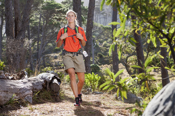 Woman hiking with backpack in woods