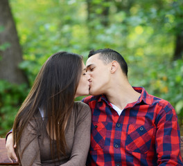 Couple kissing at the bench in park