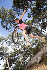 Woman jumping with mountain bike over log in woods