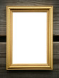 Empty golden picture frame on wooden wall