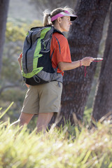 Woman hiking with backpack and compass in woods