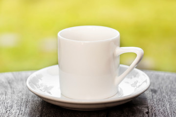 White cup of coffee on table with landscape background