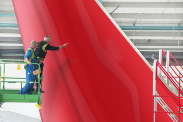 Engineers inspecting tail of passenger jet in hangar