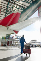 Engineer with tool box below passenger jet in hangar