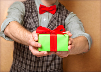 male hands holding small gift with ribbon.