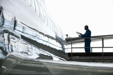 Engineer at tail of passenger jet in hangar