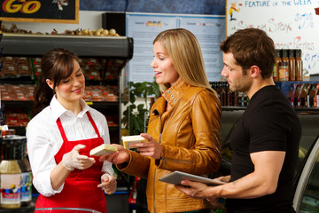 Shopping couple discussing with clerk at butcher shop