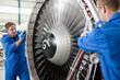 Engineers repairing engine of passenger jet in hangar