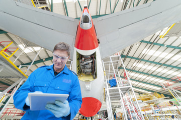 Engineer with digital tablet below passenger jet in hangar