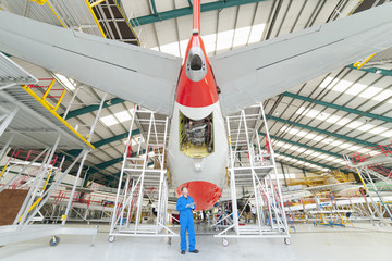 Engineer standing below passenger jet in hangar