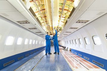 Engineers inspecting wiring on inside passenger jet
