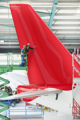 Engineers on lift inspecting tail of passenger jet in hangar