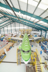 High angle view of engineers and passenger jet in hangar
